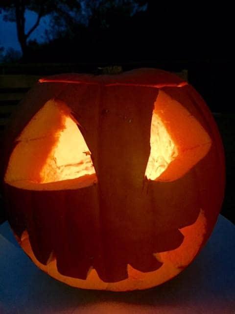 carved-pumpkin-face-lit-up-night-time